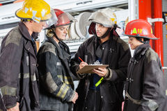 Team Of Firefighters Discussing Over Clipboard Royalty Free Stock Photography