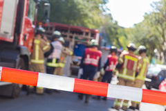 Team of firefighters by firetruck on accident location. Royalty Free Stock Images