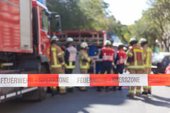 Team of firefighters by firetruck on accident location. Team of blured firefighters by firetruck on protected accident site. Focus on red and white security Royalty Free Stock Photo