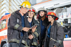 Team Of Firefighters Using Digital Tablet. Against firetruck at station Royalty Free Stock Images
