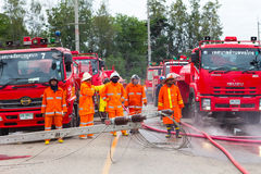 Team fireman with the fire department. PHICHIT THAILAND-AUGUST 7:Team Thailand officers or firefighters standing waiting in front of the fire truck lot. On stock images