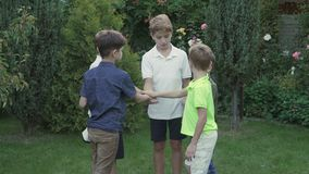 Five brothers put hands one on another in the garden stock video footage
