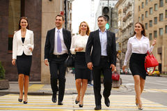 Team of five business people confidently striding along the summ Stock Images