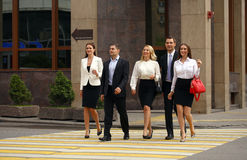 Team of five business people confidently striding along the summ Royalty Free Stock Image