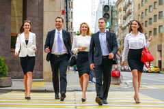 Team of five business people confidently striding along the summ Stock Image