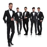 Team of five groomsmen in tuxedoes with leader in front royalty free stock photo