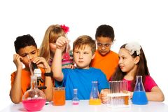 Chemistry class fun for kids. Team of five kids experimenting on chemistry lesson with test tubes, liquids and flasks, isolated on white Royalty Free Stock Photography