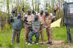 Team of five men with flag play paintball Stock Photo