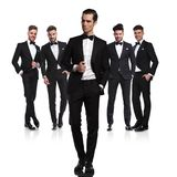 Team of five relaxed groomsmen standing with leader in front royalty free stock photography