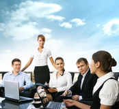 A team of five young persons is working together. A team of five young businesspersons is working together in a modern coffee shop. The image is taken outdoors Royalty Free Stock Image