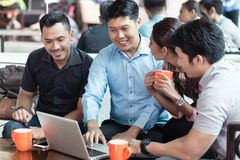 Team of four dedicated employees working together. Team of four dedicated employees sitting in front of a laptop while working together at an innovative business stock image