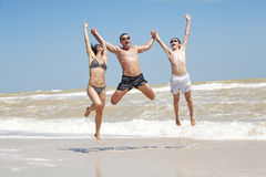 Team of friends jumping at the beach Stock Images