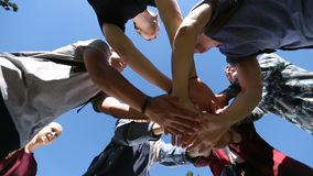 Team of friends showing unity joining hands. Closeup pile of college friends` hands showing unity while standing huddle on university campus over blue sky stock footage