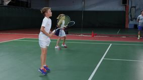 Team of girl and boy playing tennis on indoor court. Young players practicing stock footage