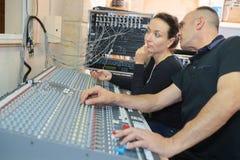 Team gli ingegneri che lavorano allo scrittorio di miscelazione in studio di registrazione Fotografia Stock
