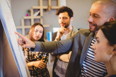 Team of graphic designer discussing chart on white board. In the office Stock Photography