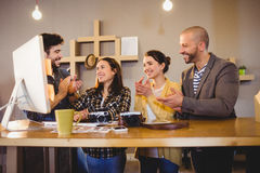 Team of graphic designers applauding a colleague. In office Royalty Free Stock Image