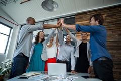 Team of graphic designers giving high five to each other. In office stock photography