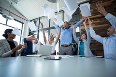 Team of graphic designers throwing documents up in air Royalty Free Stock Photo