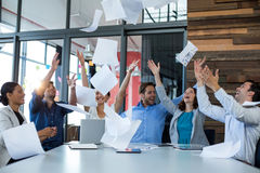 Team of graphic designers throwing documents up in air Royalty Free Stock Photography