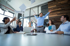 Team of graphic designers throwing documents up in air Stock Photos