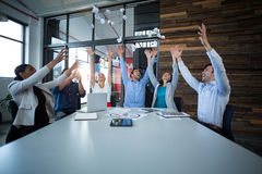 Team of graphic designers throwing paper ball up in air Stock Photo