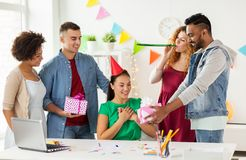 Team greeting colleague at office birthday party. Corporate, celebration and people concept - happy team with gifts greeting surprised colleague at office Royalty Free Stock Image