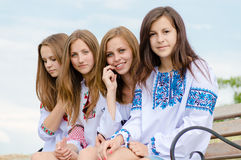 Team or group of 4 blond & brunette charming girlfriends young beautiful women sitting on bench happy smile & looking at camera Royalty Free Stock Image