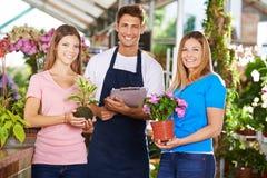 Team group in nursery shop. Happy gardener team group in nursery shop with plants and flowers stock image