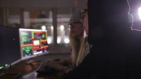 Team of hackers, hacking computers, working in dark room. HD stock video footage