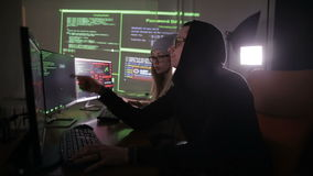 Team of hackers, hacking computers, working in dark room.