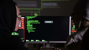 Team of hackers, hacking computers, working in dark room. HD stock footage