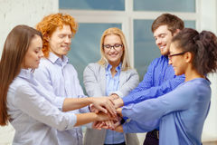 Team with hands on top of each other in office Royalty Free Stock Photos
