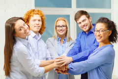 Team with hands on top of each other in office Stock Images