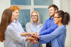 Team with hands on top of each other in office Stock Photo