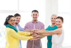 Team with hands on top of each other in office Royalty Free Stock Photography