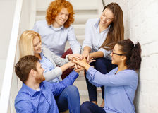 Team with hands on top of each other on staircase. Business, office, gesture and startup concept - smiling creative team with hands on top of each other sitting royalty free stock image