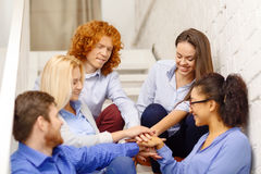 Team with hands on top of each other on staircase Royalty Free Stock Photography
