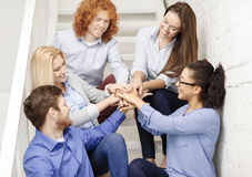 Team with hands on top of each other on staircase Stock Images