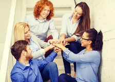 Team with hands on top of each other on staircase Royalty Free Stock Images