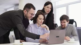 Team of business people looking at laptop screen during creative meeting stock video