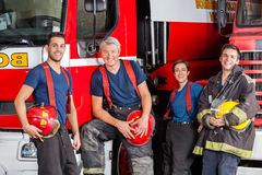 Team Of Happy Firefighters At Fire Station. Team of happy firefighters leaning on trucks at fire station Stock Images