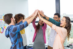 Team of happy graphic designers giving high five. In office Royalty Free Stock Image