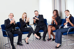 Team of happy successful businesspeople. Portrait of a team of happy successful businesspeople sitting together smiling and celebrating at the office stock images
