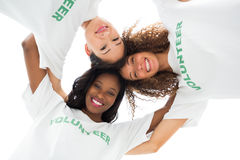 Team of happy volunteers embracing and looking down at camera. On white background Royalty Free Stock Image