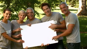 Team of happy volunteers in the park showing sign stock video footage