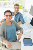 Team of happy young designers at desk looking at camera Royalty Free Stock Image