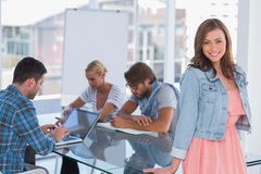 Team having meeting with one woman standing and smiling at camer Stock Photos