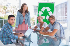 Team having meeting about recycling and smiling at camera Royalty Free Stock Images