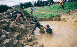 Team helping to cross mud pit in a test of extreme obstacle race Royalty Free Stock Image